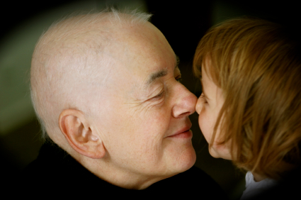 and older woman with a shaved head is rubbing noses with a small child. Both are smiling at each other.