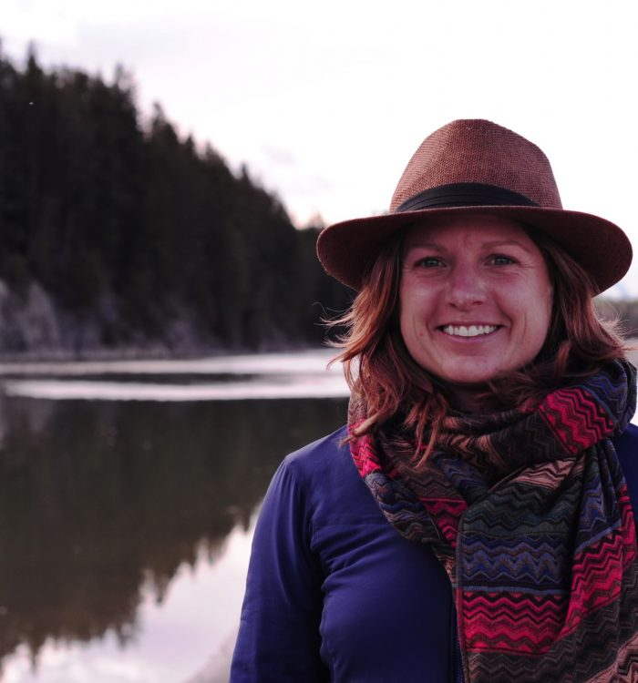 Smiling woman with a hat and scarf in front of a forest lined lake.